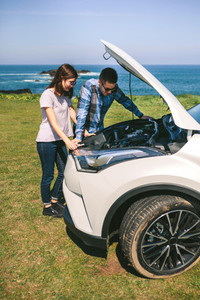 Young couple tries to fix the broken down car