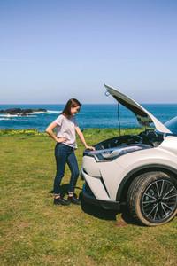 Girl looking engine of broken down car