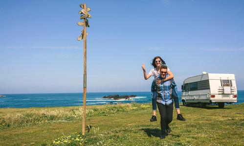 Young man piggybacking his girlfriend near the coast