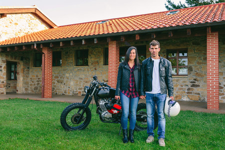 Couple posing holding hands and custom motorcycle
