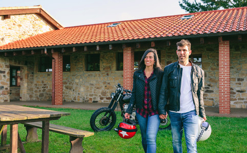Couple walking holding hands and custom motorcycle