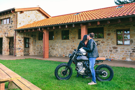 Couple kissing with custom motorcycle