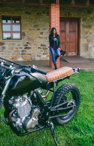 Woman waiting looking at the mobile with custom motorcycle