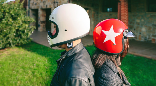 Couple posing with motorcycle helmets