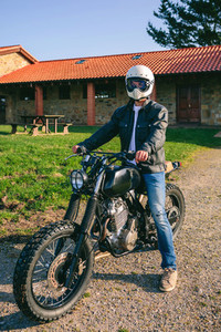 Man with helmet riding custom motorbike