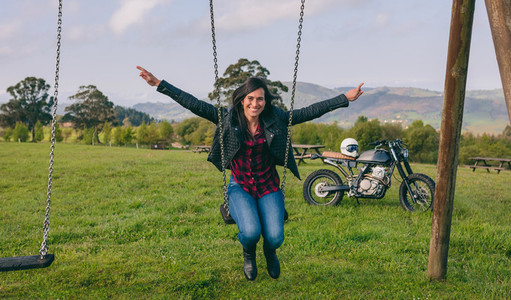 Young woman swinging with motorcycle in the background