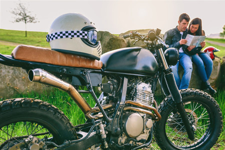Custom motorcycle with helmet and young couple looking at a map