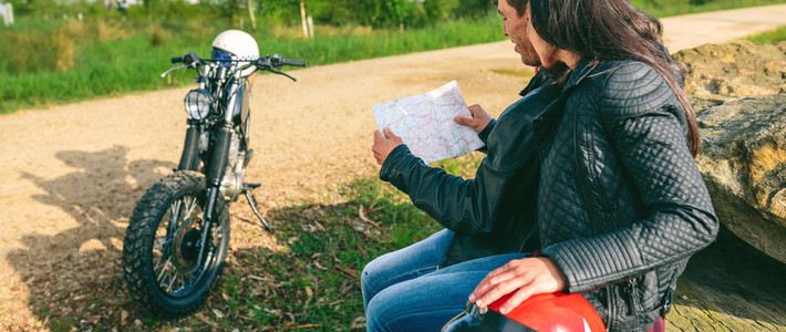 Couple sitting looking at a map with motorcycle