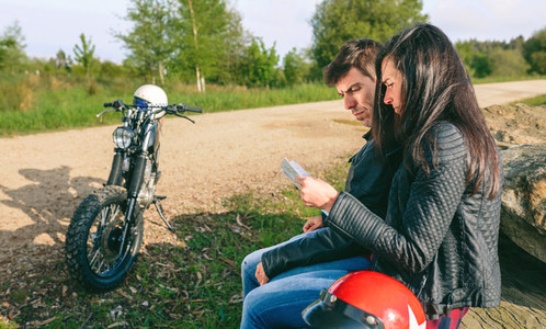 Lost couple sitting looking at a map with motorcycle