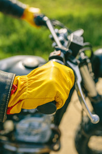 Bikers hand with gloves grabbing the handlebar