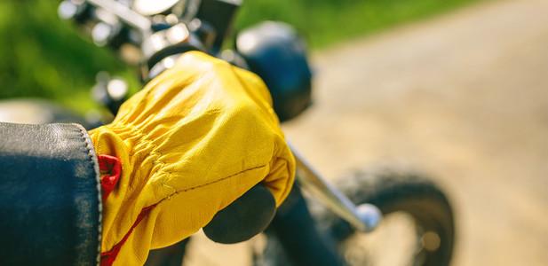 Bikers hand with gloves grabbing the handlebar