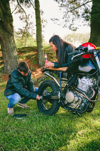 Man fixing his motorcycle while his girlfriend looks at him