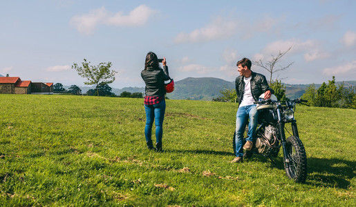 Couple making a landscape photo during a motorcycle trip