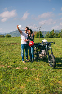 Couple taking a selfie with a motorcycle