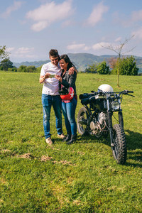 Couple looking mobile with a motorcycle
