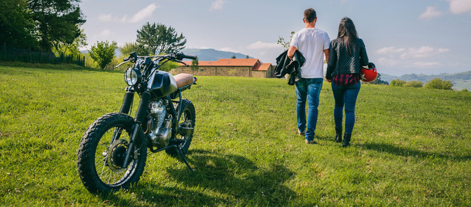 Couple walking on the field holding hands and motorbike