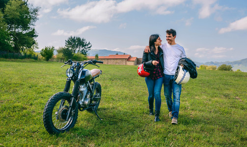 Couple walking on the field embraced and motorbike