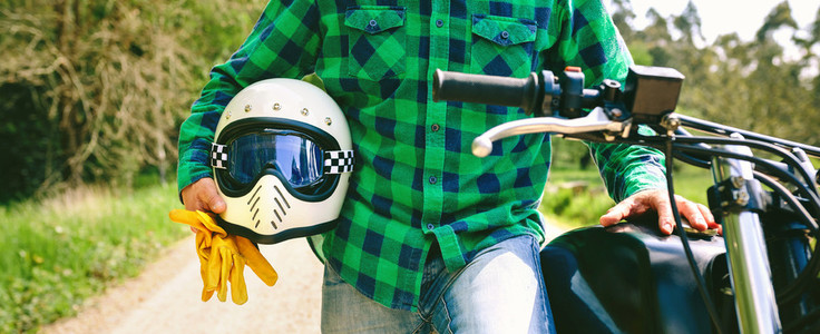 Man posing with motorcycle  helmet and gloves