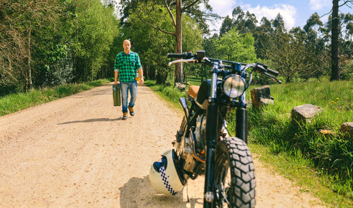 Man with gasoline can walking to custom vintage motorbike