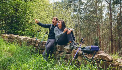 Happy couple pausing while doing trekking