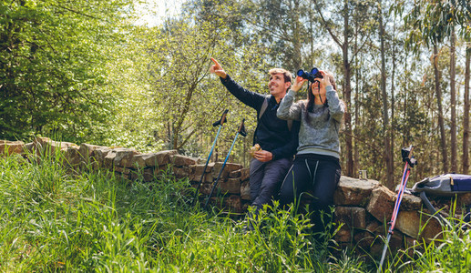 Couple doing trekking looking with binoculars