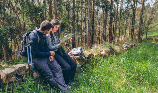 Couple doing trekking sitting looking at a map