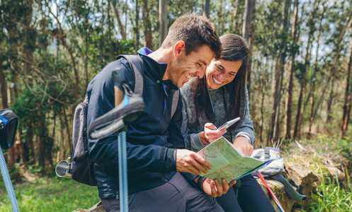 Couple doing trekking sitting looking mobile and map