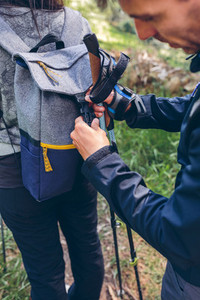 Hiker closing his partners backpack
