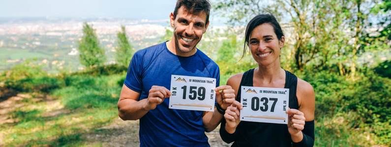 Man and woman showing their trail race number