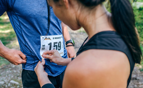 Trail athlete placing race number to her partner