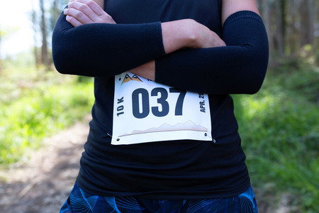 Unrecognizable female trail athlete posing with race number