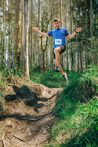 Man jumping participating in trail race