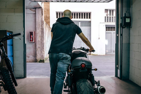 Man with custom motorbike leaving the garage