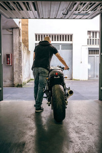 Man with custom motorbike leaving the garage