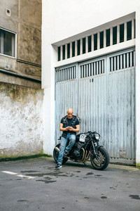 Biker looking mobile sitting on motorcycle