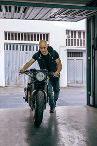 Biker taking motorbike to the garage
