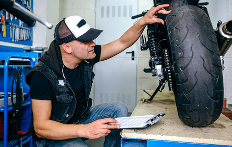 Mechanic checking wheel of a customized motorcycle