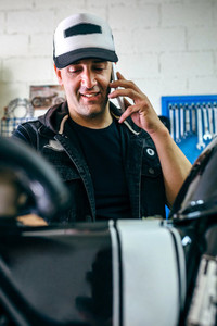 Mechanic talking phone while fixing motorbike