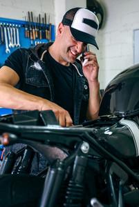 Mechanic talking phone while fixing motorbike