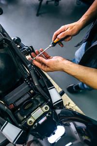 Mechanic repairing customized motorcycle