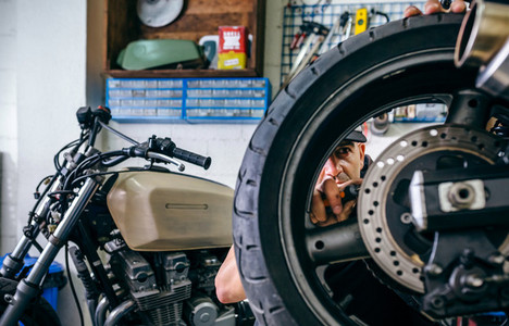 Mechanic fixing custom motorcycle wheel