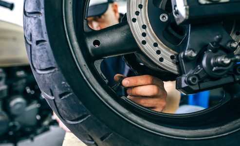 Mechanic placing motorcycle wheel valve