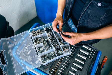 Mechanics hands choosing screws from a tool box