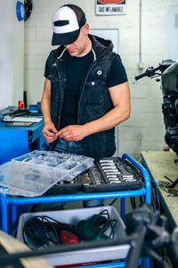 Mechanic choosing screws from a tool box