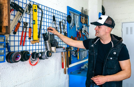 Mechanic in his workshop taking tools