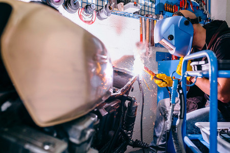 Motorcycle mechanic welding in the workshop