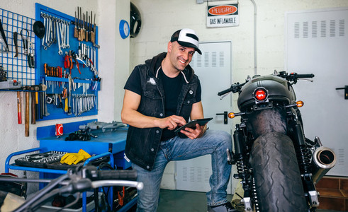 Mechanic checking custom motorcycle with tablet