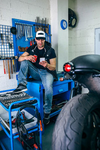 Motorcycles mechanic resting having a beer