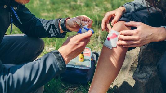 Man healing knee to woman who has been injured trekking