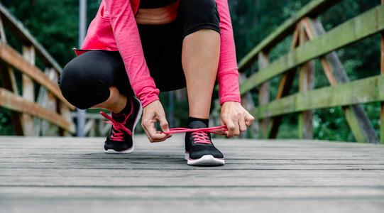 Sportswoman tying shoelace preparing to run